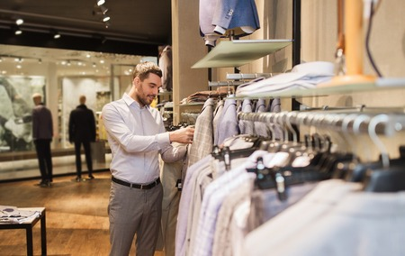 fashion clothes: sale, shopping, fashion, style and people concept - elegant young man choosing clothes in mall or clothing store Stock Photo