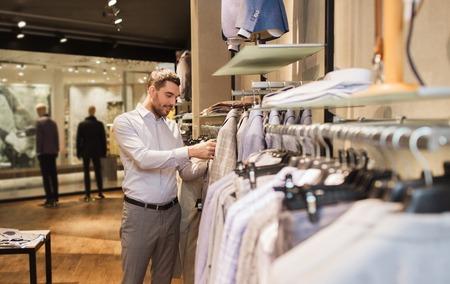 moda ropa: venta, compras, moda, estilo y concepto de la gente - hombre joven elegir ropa elegante en centro comercial o tienda de ropa