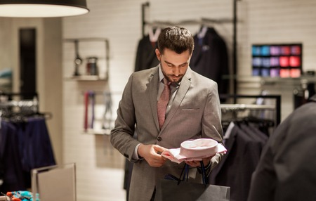 lifestyle: sale, shopping, fashion, style and people concept - elegant young man in suit choosing shirt in mall or clothing store Stock Photo