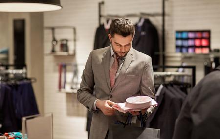 verkoop, winkelen, mode, stijl en mensen concept - elegante jonge man in pak kiezen shirt in winkelcentrum of kledingwinkel