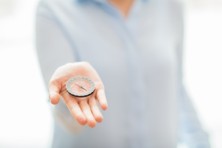 discovery: business, people, navigation and strategy concept - close up of woman hand holding compass Stock Photo