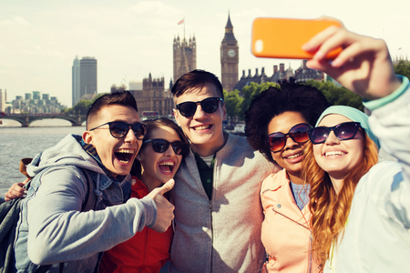 tourism, travel, people, leisure and technology concept - group of smiling teenage friends taking selfie with smartphone over houses of parliament and thames river in london background Stock Photo