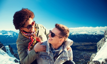 snowcovered: friendship, travel, tourism and people concept - happy international teenage couple in shades having fun over alps mountains in austria background Stock Photo