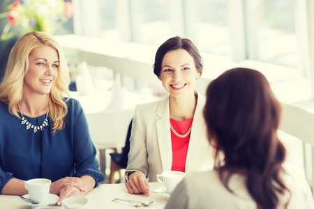 middle age women: people, communication and lifestyle concept - happy women drinking coffee and talking at restaurant Stock Photo
