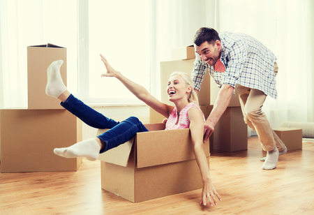 move in: home, people, moving and real estate concept - happy couple having fun and riding in cardboard boxes at new home