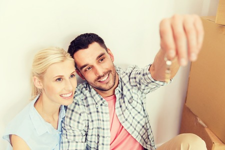 'young things': home, people and real estate concept - happy couple with key and cardboard boxes moving to new place Stock Photo