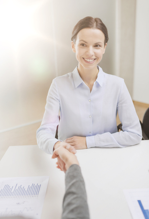busineswoman: business and office concept - smiling businesswoman shaking hand in office Stock Photo