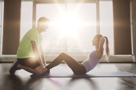fitness training: fitness, sport, training, teamwork and people concept - woman with personal trainer doing sit ups in gym Stock Photo