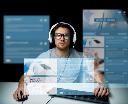 technology, communication, mass media, virtual reality and people concept - young man in headset and eyeglasses with pc computer keyboard over virtual screens Фото со стока