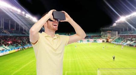 3d technologie, virtuele werkelijkheid, sport, vermaak en mensenconcept - gelukkige jonge mens met virtuele werkelijkheidshoofdtelefoon of 3d glazen over voetbalgebied op stadionachtergrond Stockfoto