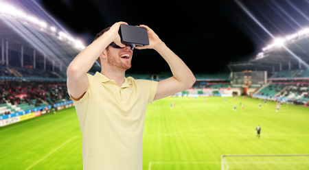 3d technology, virtual reality, sport, entertainment and people concept - happy young man with virtual reality headset or 3d glasses over football field on stadium background