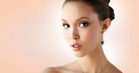 beauty, people, make up and luxury concept - close up of beautiful asian woman or bride with earring over beige background