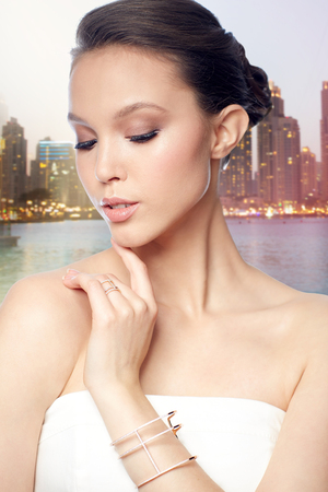 bride bangle: beauty, jewelry, wedding accessories, people and luxury concept - beautiful asian woman or bride with golden ring and bracelet over evening dubai city lights and skyscrapers background