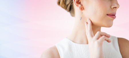 glamour luxury: glamour, beauty, jewelry and luxury concept - close up of beautiful woman face with gold and diamond earring over rose quartz and serenity gradient background