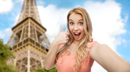 emotions, expressions and people concept - happy smiling young woman taking selfie and showing thumbs up over paris eiffel tower background