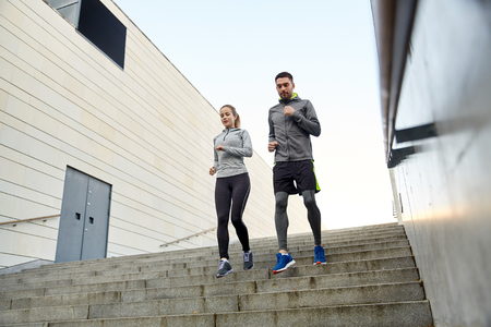 downstairs: fitness, sport, people and lifestyle concept - happy couple running downstairs in city