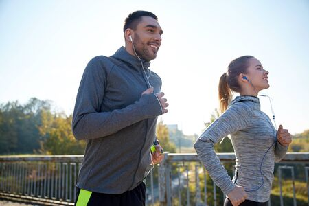 personas corriendo: fitness, deporte, la gente y el concepto de estilo de vida - pareja feliz con auriculares correr al aire libre