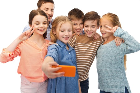 childhood, friendship, technology and people concept - happy children talking selfie by smartphone Stock Photo