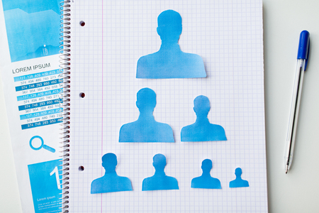 demografia: business, people, employment, career and hiring concept - close up of paper human shapes on notebook Foto de archivo