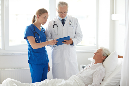 computer age: medicine, age, health care and people concept - doctor and nurse with tablet pc computer visiting senior patient woman at hospital ward