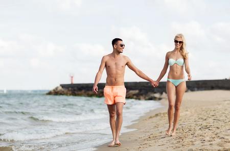 manos entrelazadas: concepto de amor, los viajes, el turismo, el verano y la gente - sonriente pareja de vacaciones en traje de baño y gafas de sol de la mano y caminar en la playa