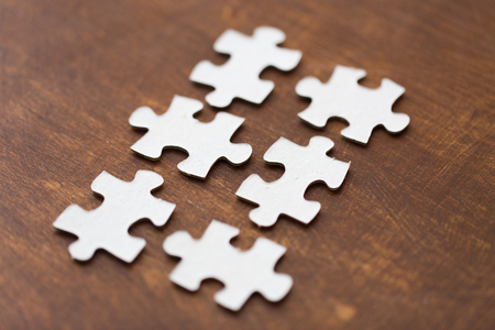 business puzzle: business and connection concept - close up of puzzle pieces on wooden surface