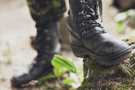 war, hiking, army and people concept - close up of soldier feet in army boots in forest
