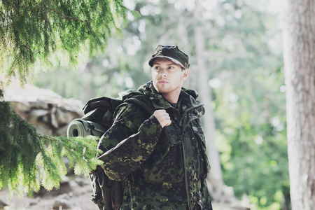 corps: war, hiking, army and people concept - young soldier or ranger with backpack walking in forest
