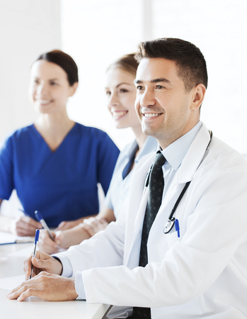 white coat: hospital, profession, medical education, people and medicine concept - group of happy doctors meeting on presentation at hospital Stock Photo