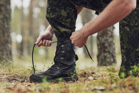 corps: war, hiking, army and people concept - close up of soldier boots and hands tying bootlaces in forest