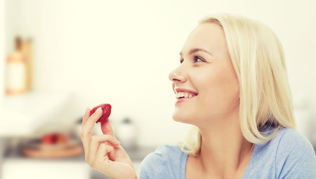 over eating: healthy eating, food, fruits, diet and people concept - happy woman eating strawberry over kitchen background Stock Photo