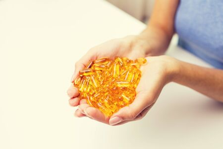 home health care: healthy eating, medicine, health care, food supplements and people concept - close up of woman hands holding pills or fish oil capsules at home Stock Photo