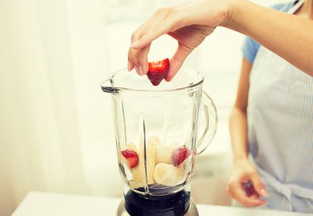 licuadora: alimentación saludable, cocinar, comida vegetariana, la dieta y el concepto de personas - cerca de la mujer con el mezclador haciendo plátano batido de fresa fruta en el país