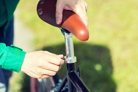 fixed: people, vehicle, eisure and lifestyle - close up of man adjusting fixed gear bike saddle high Stock Photo