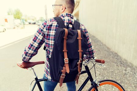 people, travel, tourism, leisure and lifestyle - young hipster man with fixed gear bike and backpack on city street