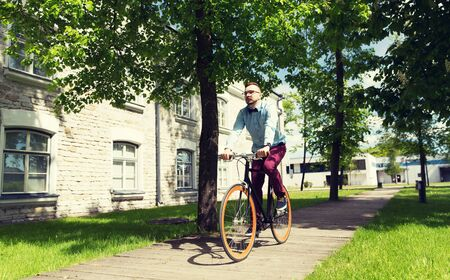 fixed: people, style, leisure and lifestyle - happy young hipster man riding fixed gear bike on city street