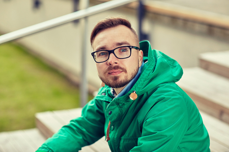 people, style, leisure and lifestyle - happy young hipster man in eyeglasses and jacket sitting on stairs in city Stock Photo