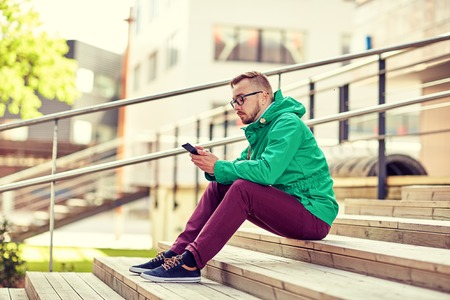 people, style, technology and lifestyle - young hipster man with smartphone sitting on stairs in city Stock Photo