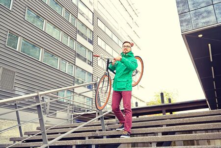 going down: people, sport, style, leisure and lifestyle - young hipster man carrying fixed gear bike on shoulder down stairs in city Stock Photo