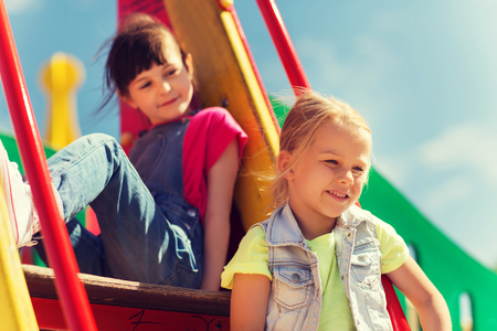 children clothing: summer, childhood, leisure, friendship and people concept - happy kids on children playground climbing frame Stock Photo