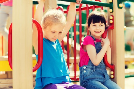 kids outside: summer, childhood, leisure, friendship and people concept - group of happy little girls on children playground climbing frame Stock Photo
