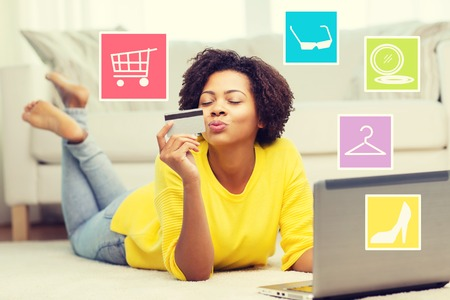 happy african: people, internet bank, online shopping, technology and e-money concept - happy african american young woman lying on floor with laptop computer and credit card at home over internet icons Stock Photo