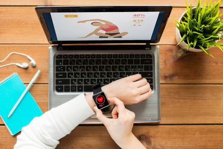 cardio fitness: healthcare, fitness, people and technology concept - close up of woman with smart watch and laptop computer on wooden table with sport application and heart rate on screens Stock Photo