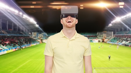 mediated: 3d technology, virtual reality, sport, entertainment and people concept - happy young man with virtual reality headset or 3d glasses over football field on stadium background