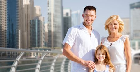 urban parenting: summer holidays, travel, tourism, vacation and people concept - happy family over dubai city street background Stock Photo