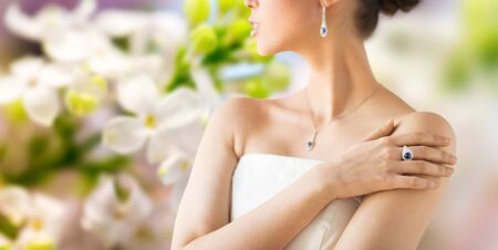 glamour luxury: glamour, beauty, jewelry and luxury concept - close up of beautiful woman with finger ring over natural spring lilac blossom background