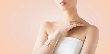 bride bangle: glamour, beauty, jewelry and luxury concept - close up of beautiful woman with golden ring and bracelet over beige background Stock Photo