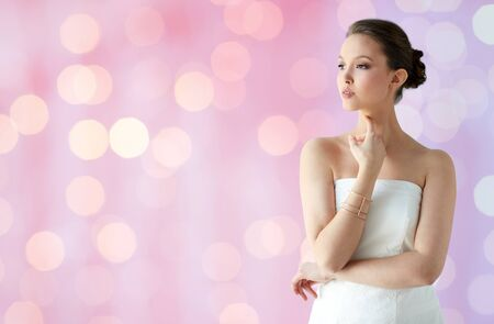 bride bangle: beauty, jewelry, wedding accessories, people and luxury concept - beautiful asian woman in white dress or bride with golden bracelet over holidays lights background