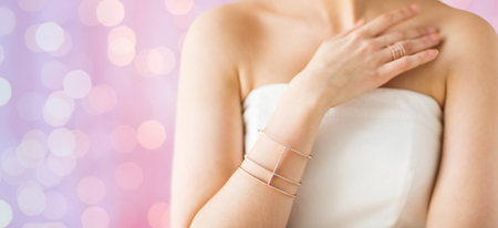 bride bangle: glamour, beauty, jewelry and luxury concept - close up of beautiful woman with golden ring and bracelet over pink holidays lights background