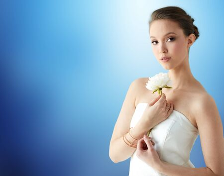 wristlet: beauty, jewelry, people and luxury concept - beautiful asian woman or bride in white dress with peony flower, golden ring and bracelet over blue background